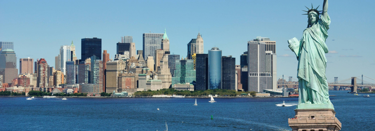 NYC skyline in daytime showing statue of liberty